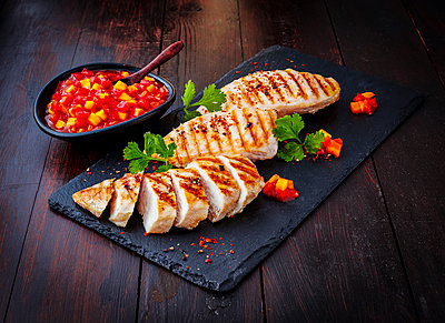 Chicken breast fillet with bell pepper chutney on slate - p300m2012814 by Kai Schwabe