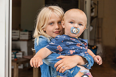 Portrait of girl holding baby boy brother at home - p300m2030357 by Tom Chance