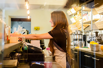Young woman working at the counter in a cafe - p300m2140356 von Giorgio Fochesato