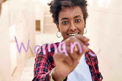 Smiling young female hipster writing WOMAN while celebrating Womens Day - p300m2241790 by Veam