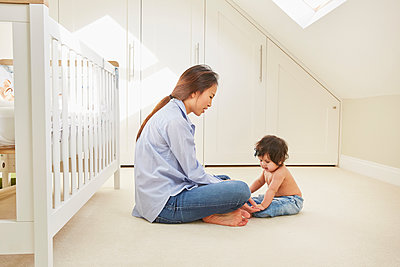 Woman sitting on floor playing with baby daughter - p429m1448156 by Emma Kim