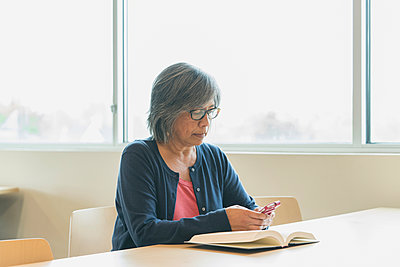Filipino woman texting on cell phone in library - p555m1532320 by Hill Street Studios