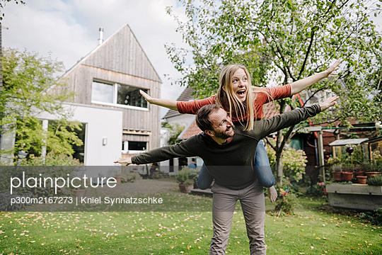 Cheering couple pretending to fly, standing in their garden - p300m2167273 von Kniel Synnatzschke