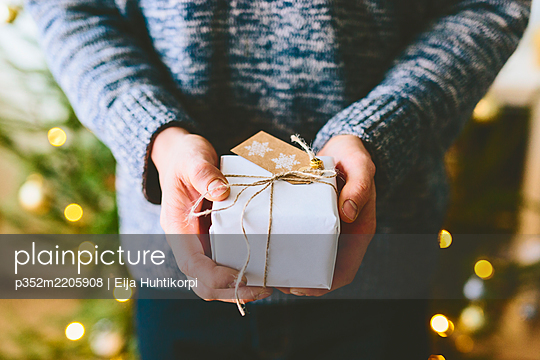 Finland, Man holding christmas gift against christmas tree - p352m2205908 by Eija Huhtikorpi