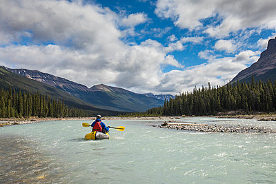 Rear view of person kayaking (Packrafting) in scenic valley, Banff. - p1166m2213521 by Cavan Images