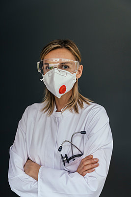 Portrait of doctor wearing FFP3 mask and safety glasses against grey background - p300m2199266 by Mareen Fischinger