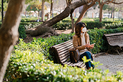 Mature woman with protective face mask holding mobile phone while sitting at park - p300m2265858 by Ezequiel Giménez