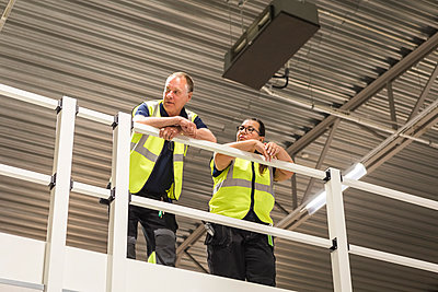 Low angle view of coworkers leaning on railing at distribution warehouse - p426m2018830 by Maskot