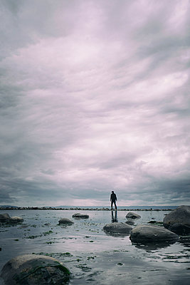 Man standing on shingle bank looking into sea - p597m2093431 by Tim Robinson