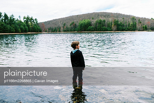 Little boy in red rubber boots walking through blue pristine water - p1166m2268865 by Cavan Images