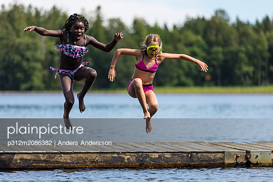 Girls jumping into lake - p312m2086382 by Anders Andersson
