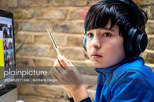 UK, Boy (10-11) in headphones having on-line lesson - p924m2271246 by Bonfanti Diego