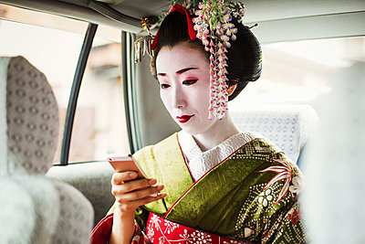 A woman dressed in the traditional geisha style, wearing a kimono and obi, with an elaborate hairstyle and floral hair clips, with white face makeup with bright red lips and dark eyes in a car using a smart phone.  - p1100m1185729 by Mint Images