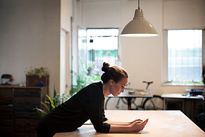 Side view of woman using smart phone while leaning on table - p1166m1098570f by Cavan Images