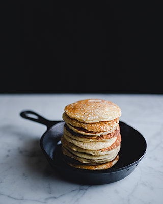 Stack of pancakes in frying pan on marble counter - p1166m1142999 by Cavan Images