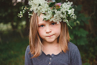 Close-up portrait of girl wearing flowers while standing at farm - p1166m2000569 by Cavan Images