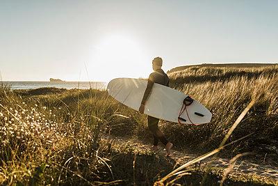 France, Bretagne, Crozon peninsula, woman walking through dunes carrying surfboard - p300m1189330 by Uwe Umstätter