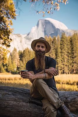 USA, California, portrait of bearded man sitting on a log in Yosemite National Park - p300m2070147 by Kike Arnaiz