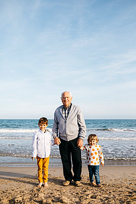 Portrait of happy grandfather standing hand in hand on the beach with his grandchildren - p300m2103173 von Josep Rovirosa