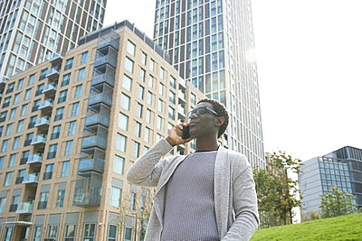 Male professional talking on mobile phone while standing against office building in downtown - p300m2241562 von Pete Muller