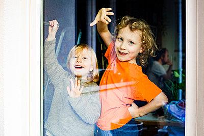 Playful siblings seen through glass door - p300m2277132 by Irina Heß