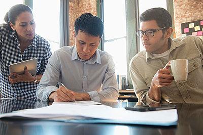 Business people watching businessman write on paperwork - p555m1304229 by Jose Luis Pelaez Inc.