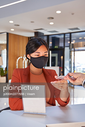 Woman wearing face mask taking cardkey from receptionist at hotel reception - p300m2277656 by Veam