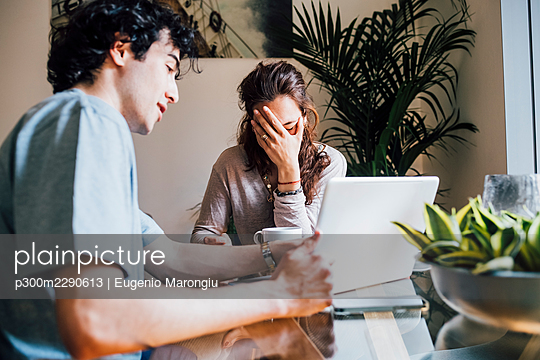 Boyfriend with laptop explaining to frustrated girlfriend at home - p300m2290613 by Eugenio Marongiu