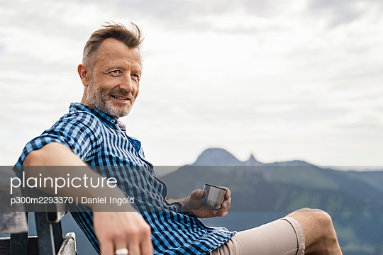 Male hiker holding cup while sitting on bench - p300m2293370 by Daniel Ingold