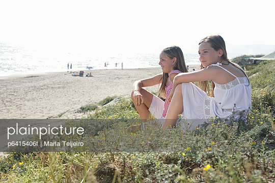 Girls sitting in flowers at beach