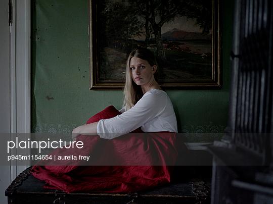 Junge Frau sitzt vor einem Gemälde - p945m1154654 von aurelia frey