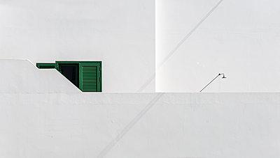 Grünes Fenster und Dusche an weisser Wand hinter weisser Grundstücksmauer - p1162m1516862 von Ralf Wilken