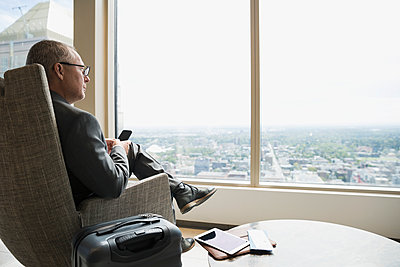 Pensive businessman with luggage texting looking out window in airport lounge - p1192m1183766 by Hero Images