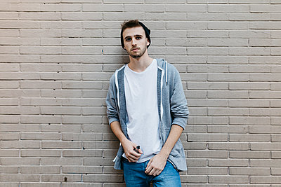 Young man standing in front of wall,  holding electronic cigarette - p300m2058889 by Josep Rovirosa