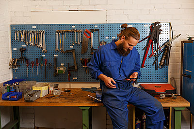 Mechanic checks his phone in a workshop in Sweden - p352m2039961 by Christian Ferm