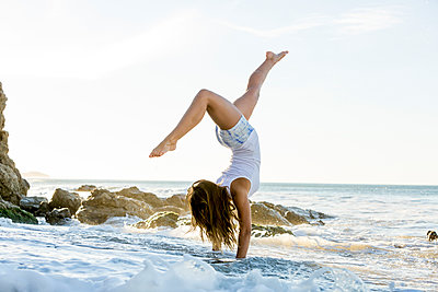 Caucasian woman doing handstand on beach - p555m1301801 by Mike Kemp