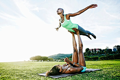 Woman and friend practicing acro yoga in park - p555m1411318 by Peathegee Inc