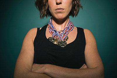 Frau mit mehreren Medaillen um den Hals - p586m984379 von Kniel Synnatzschke