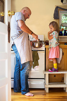 Girl on stool watching father whisking food in kitchen - p924m1557838 by Kinzie Riehm