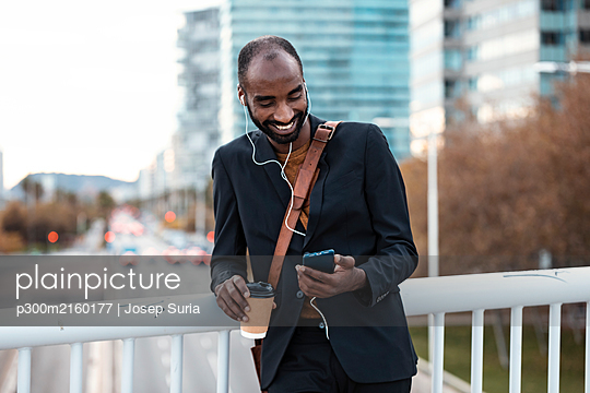 Smiling young businessman with coffee to go listening music with earphones and smartphone - p300m2160177 von Josep Suria