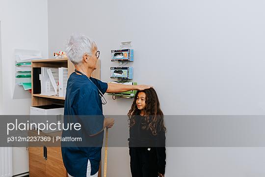 Doctor measuring girl in office - p312m2237369 by Plattform