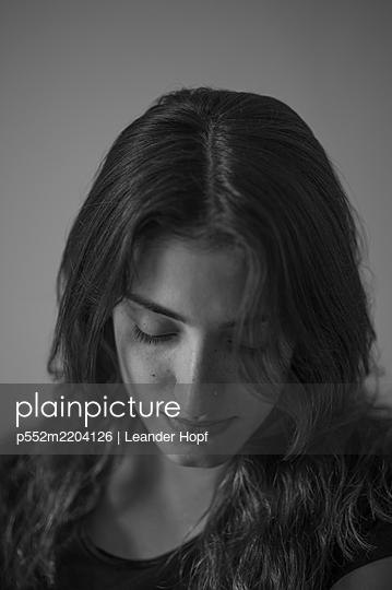 Dark-haired woman looking down - p552m2204126 by Leander Hopf