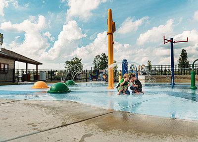 Siblings enjoying at water park against sky - p1166m1174187 by Cavan Images