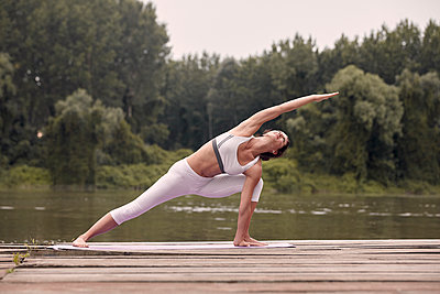 Woman practicing extended side angle pose on pier by lake against trees during sunset - p1166m2011239 by Cavan Images