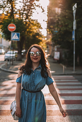Young woman wearing sunglasses while crossing road in city - p1166m2011539 by Cavan Social