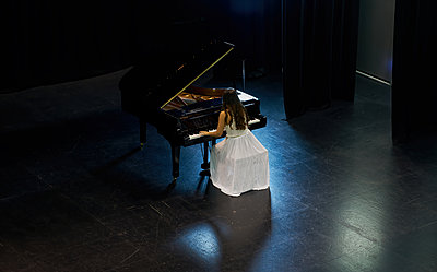 A woman with brown hair dressed in a white dress seen playing a black grand piano with the lid raised. View from above of the pianist - p1166m2152155 by Cavan Images
