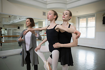 Female instructor and mentor adjusting teenage ballet dancer prodigy in dance studio - p1192m1403483 by Hero Images