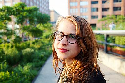 Junge Frau mit Brille schaut in die Kamera - p1301m2016055 von Delia Baum