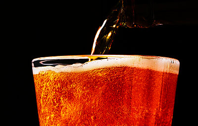 Pouring beer into glass, close-up - p1397m2184333 by David Prince