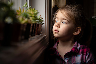 Portrait of a young girl looking out a window by succulents - p1480m2148207 by Brian W. Downs